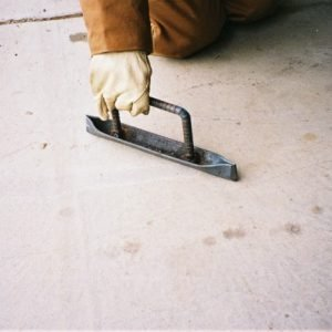 A hand held grooving tool for finishing the edges and corners of concrete floors is made from a piece of angle iron