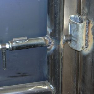 Slam latch on block gate in cattle alley latches automatically when the gate is closed